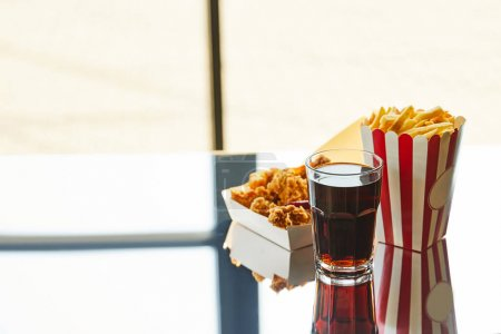 Photo for Deep fried chicken, french fries and soda in glass on glass table in sunlight near window - Royalty Free Image