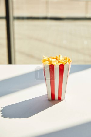 tasty french fries in striped bucket on white table in sunlight near window