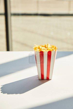 savoureuses frites dans un seau rayé sur une table blanche à la lumière du soleil près de la fenêtre