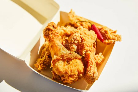 Photo for Close up view of tasty and spicy deep fried chicken with chili pepper on white table in sunlight - Royalty Free Image