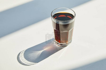Photo for Tasty soda in glass on white table in sunlight with shadow - Royalty Free Image