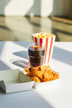 Photo for Selective focus of tasty deep fried chicken, french fries and soda in glass on white table in sunlight - Royalty Free Image