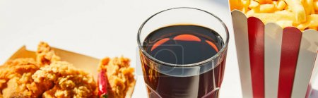 close up view of tasty deep fried chicken, french fries and soda in glass on white table in sunlight, panoramic crop