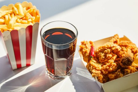 tasty deep fried chicken, french fries and soda in glass on white table in sunlight
