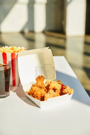 Photo for Tasty deep fried chicken, french fries and soda in glass on white table in sunlight - Royalty Free Image