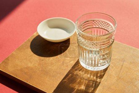 Photo pour Verre vide à facettes et bol blanc sur planche en bois à la lumière du soleil - image libre de droit