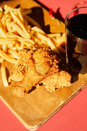 Photo for Selective focus of crispy deep fried chicken and french fries served on wooden cutting board with soda in sunlight - Royalty Free Image
