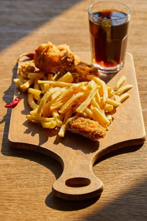 Photo for Selective focus of spicy deep fried chicken, french fries on board with soda in glass on wooden table in sunlight - Royalty Free Image