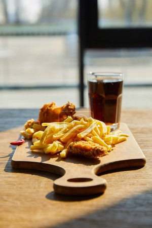 Photo for Selective focus of spicy deep fried chicken, french fries on board with soda in glass on wooden table in sunlight near window - Royalty Free Image