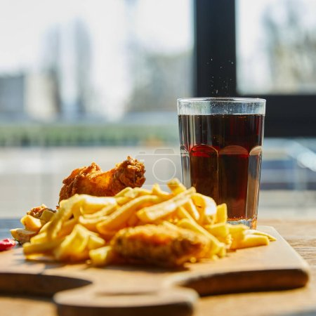 selective focus of deep fried chicken, french fries on board with soda in glass on wooden table in sunlight near window