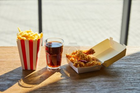 Photo for Spicy deep fried chicken, french fries and soda in glass on wooden table in sunlight near window - Royalty Free Image