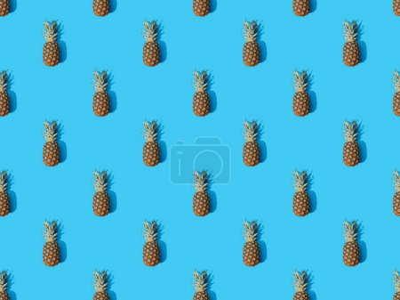 Photo for Top view of whole ripe pineapples on blue colorful background, seamless pattern - Royalty Free Image