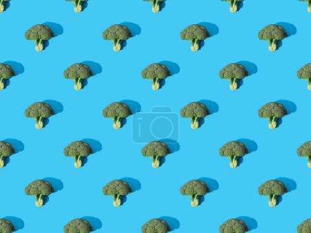 Foto de Vista superior del broccoli verde fresco en fondo azul, patrón sin costuras. - Imagen libre de derechos