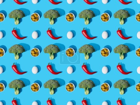 top view of fresh green broccoli, eggs, chili peppers and olives on blue background, seamless pattern