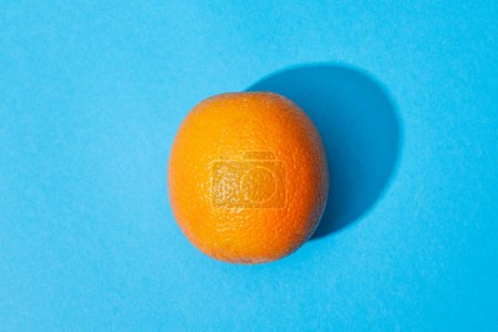 Photo for Top view of ripe orange on blue colorful background - Royalty Free Image