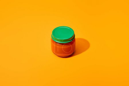 fresh tomato puree in glass jar on orange colorful background