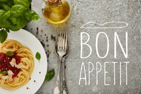 Photo for Top view of delicious spaghetti with tomato sauce on plate near basil leaves, oil and cutlery on grey textured surface with bon appetit illustration - Royalty Free Image
