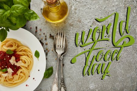 Photo for Top view of delicious spaghetti with tomato sauce on plate near basil leaves, oil and cutlery on grey textured surface with world food day illustration - Royalty Free Image