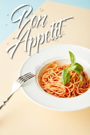 delicious spaghetti with tomato sauce in plate near fork on blue and yellow background with bon appetit illustration