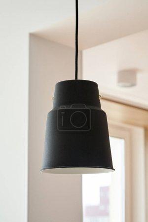 black lamp hanging near white walls in apartment