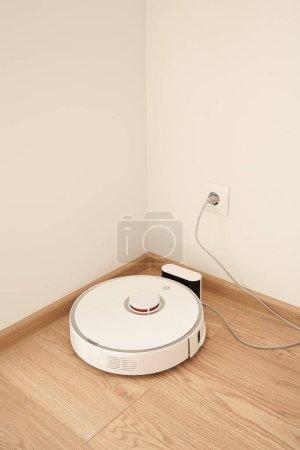 Photo pour Aspirateur robotique moderne près de la prise de courant sur le mur - image libre de droit