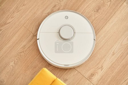 Photo for Top view of white robotic vacuum cleaner washing floor - Royalty Free Image