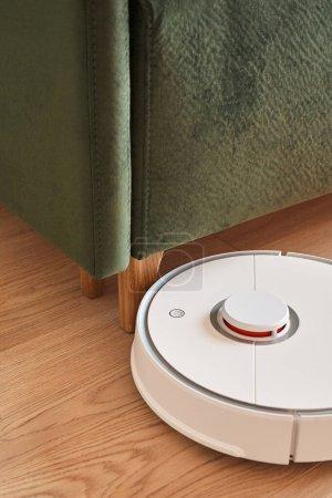 Photo for Modern robotic vacuum cleaner washing floor near green sofa - Royalty Free Image