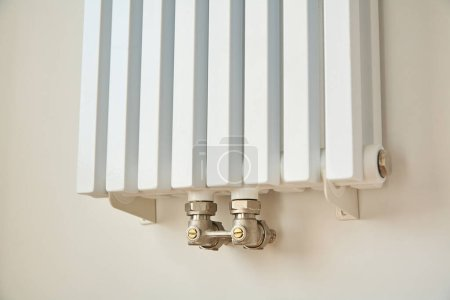 Photo for Modern heating radiator near white wall in apartment - Royalty Free Image