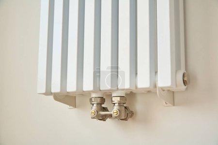 Foto de El radiador de calefacción moderno cerca de la pared blanca en los apartamentos. - Imagen libre de derechos