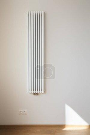 Photo pour Radiateur de chauffage blanc et moderne près du mur avec prises électriques - image libre de droit