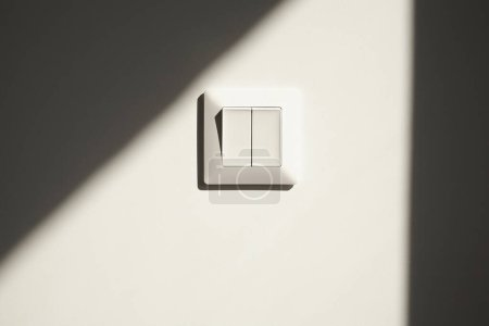 Photo for Sunshine on white switch on wall in apartment - Royalty Free Image