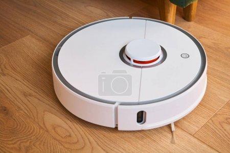 Photo pour Moderne aspirateur robotique blanc plancher de lavage - image libre de droit
