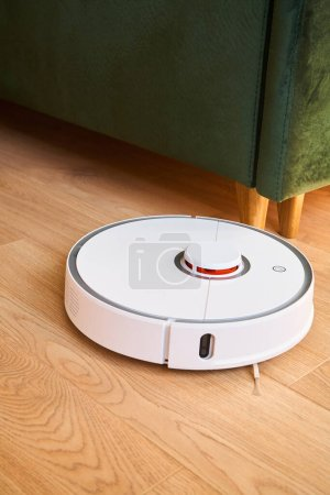 Photo for White robotic vacuum cleaner washing floor near green sofa - Royalty Free Image