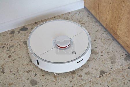 Foto de Modernas baldosas de lavavajillas con aspirador robótico en apartamento. - Imagen libre de derechos