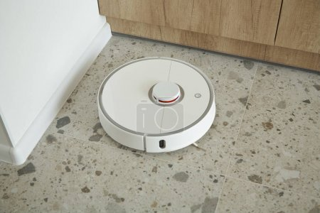 Photo for White robotic vacuum cleaner washing floor tiles in apartment - Royalty Free Image