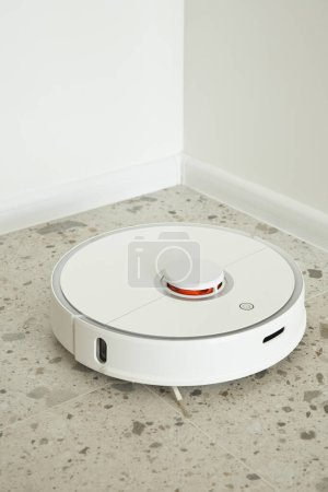 Photo for Robotic vacuum cleaner washing floor tiles near white walls - Royalty Free Image