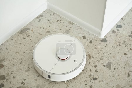 Photo for Top view of modern robotic vacuum cleaner washing floor tiles in apartment - Royalty Free Image