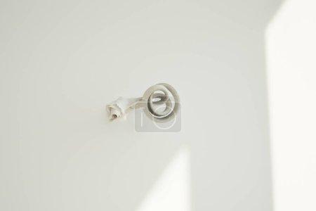 Photo pour Ensoleillement sur mur blanc avec papier déchiré près du fil de fer - image libre de droit