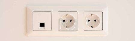 Photo pour Orientation panoramique de l'interrupteur près des prises de courant sur blanc - image libre de droit