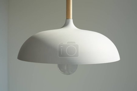 close up of white and modern lamp with light bulb near wall