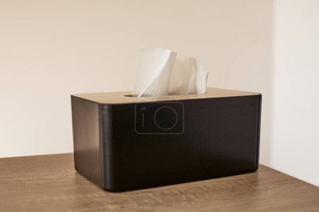 tissue box with white napkin on wooden table