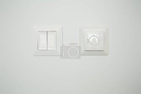 Photo pour Contrôleur de température près du panneau avec interrupteur sur mur blanc - image libre de droit