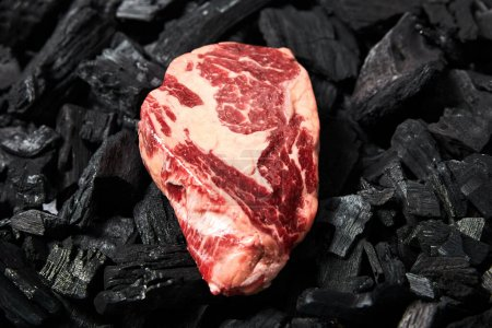 top view of fresh raw steak on black coals