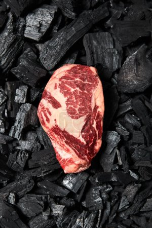 Photo for Top view of fresh raw steak on black coals - Royalty Free Image