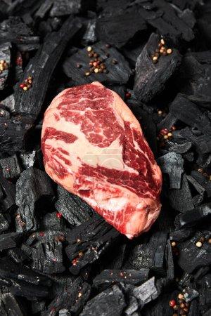 Photo pour Vue de dessus du steak cru frais sur les charbons noirs avec des grains de poivre - image libre de droit