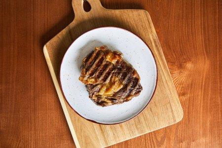 Photo pour Vue du dessus du steak frais grillé sur plaque sur planche à découper sur table en bois - image libre de droit