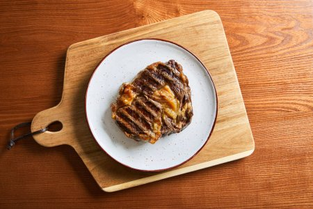 Photo for Top view of fresh grilled steak on plate on cutting board on wooden table - Royalty Free Image
