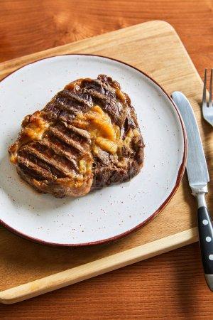 Photo pour Steak frais grillé sur assiette sur planche à découper avec couverts sur table en bois - image libre de droit