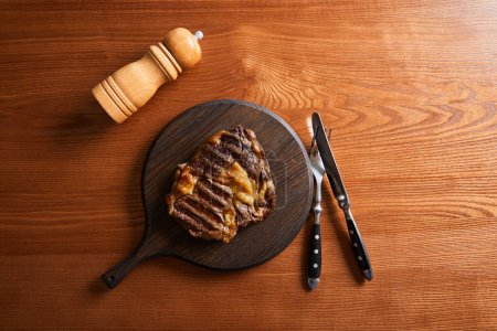 Photo for Top view of fresh grilled steak on board with cutlery and salt mill on wooden table - Royalty Free Image