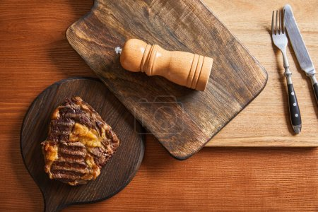 Photo for Top view of tasty grilled steak served on wooden boards with cutlery and salt mil - Royalty Free Image